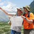 Tourist travellers with map in mountains - Stok fotoğraf