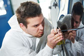 Auto mechanic painting car element — Stock Photo