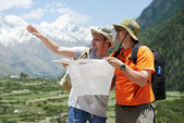 Tourist travellers with map in mountains — Stok fotoğraf