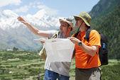 Viajantes de turismo com mapa nas montanhas — Foto Stock