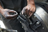 Auto mechanic hands at car repair work — Stock Photo