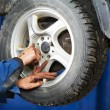 Stock Photo: Mechanic installing car wheel at service station
