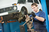 Auto mechanic at work with wrench spanner — Stock Photo