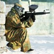 Paintball player with marker at winter outdoors - 图库照片
