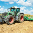 Ploughing tractor at field cultivation work - Stock Photo