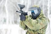 Paintball player with marker at winter outdoors — Stock Photo