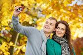 Couple at autumn outdoors — Stock Photo