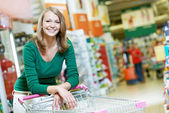 One shopping woman with cart at supermarket — Stock Photo