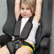 Small girl sitting in a car safety seat with seatbelt — Stock Photo