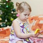 kleine lachende meisje, zittend op de bank achter kerstboom — Stockfoto