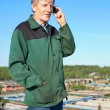 Stock Photo: Mature man in working clothes speaking on cellphone outdoor