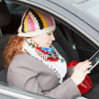 Young Caucasian woman sitting in car on passenger seat and holding electronic device — Stock Photo