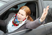 Pretty young Caucasian woman shaking hers hand and screaming sitting in car — Stock Photo