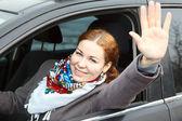 Hübsche junge caucasian frau winkte ihr hand im auto sitzen — Stockfoto