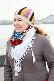 Close up portrait of happy young Caucasian female with scarf on neck. Standing outdoor — 图库照片