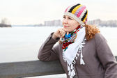 Portrait of happy young Caucasian female with scarf standing on embankment. Copy space — Stock Photo