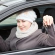 Young woman sitting in car and holding ignition keys in hand — Foto Stock