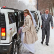 Happy newly wed couple getting in the car — Stock Photo