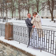 Happy bride and bridegroom standing on winter cold street — Stock Photo