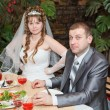 Newly married couple sit at table in restaurant, romance wedding dinner — Stock Photo #10950099