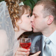 Newly wed couple with wedding gown and dark suit: groom and bride toasting with wine and enjoying there wedding day with a kiss — Stock Photo