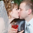 Newly wed couple with wedding gown and dark suit: groom and bride toasting with wine and enjoying there wedding day with a kiss — Stock Photo #10950103