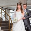 Young wedding Caucasian Russian couple standing on stairs — Stock Photo