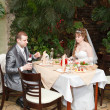 Stock Photo: Newly married couple sit at table in restaurant, romance wedding dinner