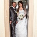 Young wedding Caucasian Russian couple standing in opened doors lift — Stock Photo