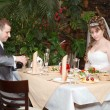 Newly married couple sit at table in restaurant, romance wedding dinner  — Stock Photo