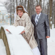 Young wedding Caucasian Russian couple holding a snowy heart on bridge. Winter season in Russia — Stock Photo