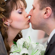 Young wedding Caucasian Russian couple kissing together and flowers between — Stock Photo #10950190