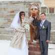 Beautiful newly merried russian couple taking pictures with lion sculpture in winter — Stock Photo