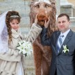Stock Photo: Beautiful newly merried russian couple taking pictures with lion sculpture in winter