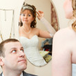 Bride looking at mirror and groom sitting near and looking at woman — Stock Photo