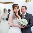 Beautiful newli merried couple in front of mirror — Stockfoto #10950217