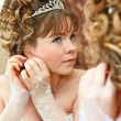 Beauty young Caucasian bride with curly hair looking in mirror and wearing earrings — Stock Photo #10950218