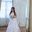 Beautiful Caucasian Russian bride in white dress and with lilies flowers — Stock Photo #10950226