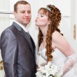 Young wedding Caucasian Russian couple. Bride kissing groom in cheek — Stock Photo