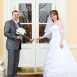 Young wedding Caucasian Russian couple standing in front of the door — Stock Photo