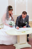 Bride and bridegroom signing marriage form — Stock Photo
