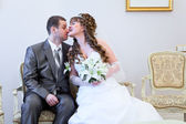 Beautiful bride jokingly bites bridegrooms nose — ストック写真