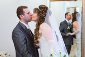 Young wedding Caucasian Russian couple kissing together. Reflection in mirror — Stock Photo
