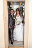 Young wedding Caucasian Russian couple standing in opened doors lift — Stock Photo