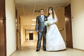 Young wedding Caucasian Russian couple standing in long corridor — Stock Photo