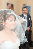 Beauty Caucasian bride in veil and groom standing on background and looking at woman — Stock Photo