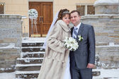 Beautiful nealy merried couple standing in front of the building in winter — Stock Photo