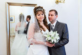 Beautiful newli merried couple in front of the mirror — Stock Photo