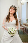 Beautiful Caucasian Russian bride in white dress and with lilies flowers — Stock Photo