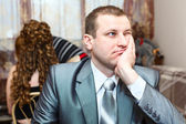 Tired Caucasian Russian bridegroom waiting for bride during wedding preparations in domestic room — Stock Photo